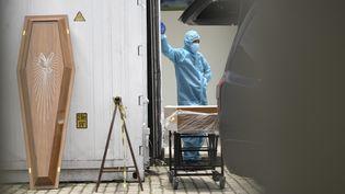 Des cercueil sont emportés dans un cimetière dédiés aux décès Covid-19 par des professionnels de santé à Rio de Janeiro (Brésil), le 8 décembre 2020. (FABIO TEIXEIRA / ANADOLU AGENCY /  AFP)