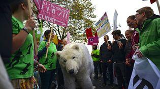 Des militants pro-environnement manifestent avec un ours polaire en peluche à l'ouverture de la COP23 à Bonn. (PHILIPP GUELLAND / EPA)
