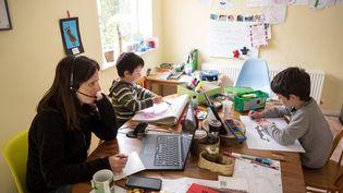 Une mère de famille travaille avec son ordinateur alors que ses enfants dessinent. Photo d'illustration. (OLI SCARFF / AFP)