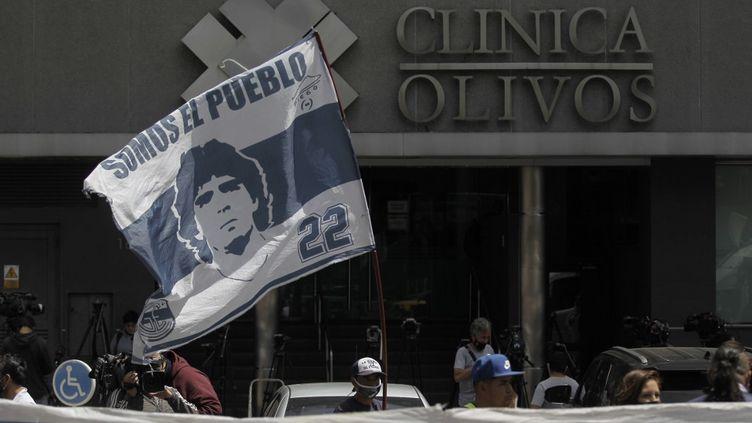 Plusieurs supporters argentins se sont rassemblés devant l'hôpital privé dans lequel s'est fait opéré Diego Maradona début novembre. (EMILIANO LASALVIA / AFP)