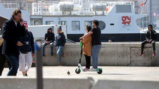 Des utilisateurs de trottinettes électriques, sur le Vieux Port de Marseille, le 25 mars 2019. (VALLAURI NICOLAS / MAXPPP)