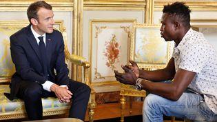 Le président de la République, Emmanuel Macron et Mamoudou Gassama, jeune Malien sans-papiers qui a sauvé un enfant, le 28 mai 2017 à l'Elysée. (THIBAULT CAMUS / AFP)