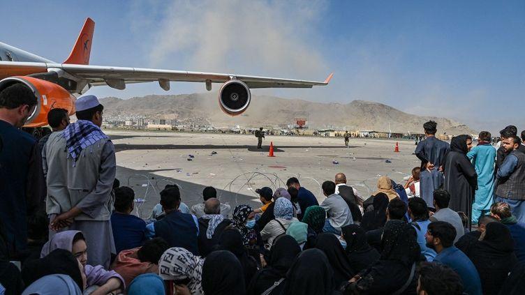 Des Afghansattendent surle tarmac de l'aéroport de Kaboul pour tenter de fuir le pays, le 16 août 2021. (WAKIL KOHSAR / AFP)