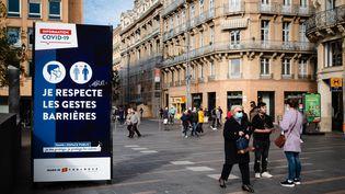 Des personnes marchent dans une rue de Toulouse (Haute-Garonne), mardi 13 octobre 2020. (LILIAN CAZABET / HANS LUCAS / AFP)