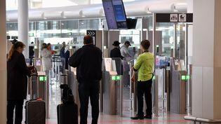 Des passagers sont photographiés le 2 mai 2016, jour de la réouverture du hall des départs à Bruxelles-Zaventem, frappé le 22 mars par des attentats. (ERIC LALMAND / BELGA MAG / AFP)
