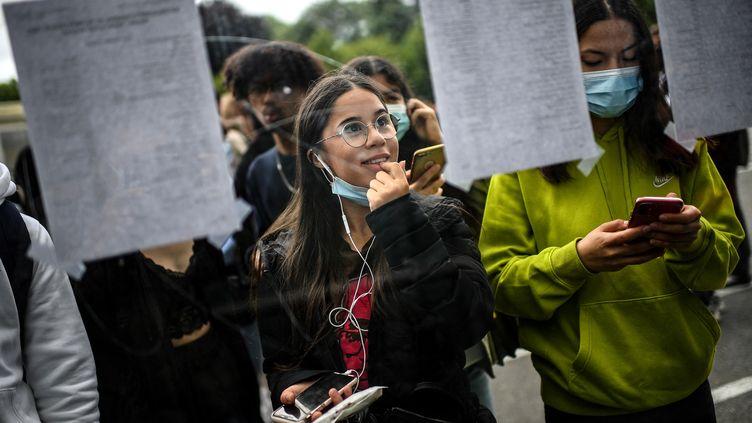 Des étudiants consultent les résultats du bac, le 6 juillet 2021 à Paris. (CHRISTOPHE ARCHAMBAULT / AFP)