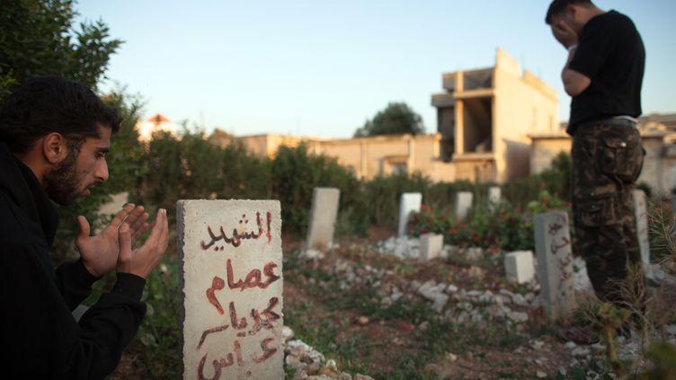 Des rebelles se recueillent dans le cimetière de la ville d'Al-Qusayr, à 15 kilomètres de Homs (Syrie), en mai 2012. (AFP )