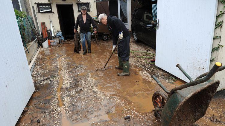 Des habitants de La Londe-les-Maures (Var) nettoient leur cour le 20 janvier 2014 après des inondations. (BORIS HORVAT / AFP)