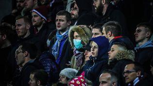 Une supportrice portant un masque de protection dans lepublic d'un match de Ligue 1 de football entre Metz et Nîmes, le 7 mars 2020. (MAXPPP)