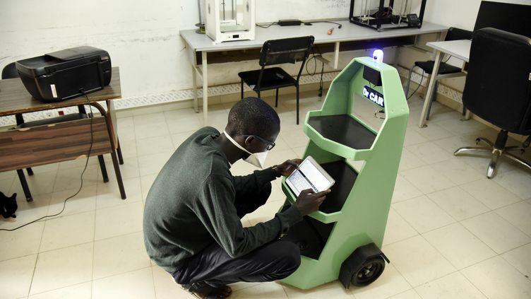"""Lamine Mouhamed Kébé, étudiant en génie mécanique, s'occupe du robot dans""""Dr Car"""", le 8 mai 2020. (SEYLLOU / AFP)"""