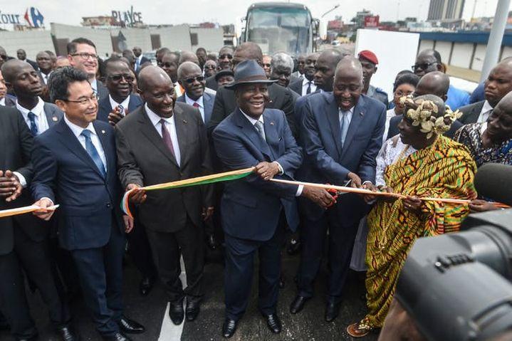 Le président ivoirien Alassane Ouattara, accompagné de plusieurs membres de son gouvernement et du chargé d'affaires de l'ambassade du Japon en Côte d'Ivoire, inaugure l'échangeur de la jonction Solibra, dans la banlieue d'Abidjan, dont la construction a été cofinancée par la Côte d'Ivoire et le Japon, le 16décembre 2019.  (SIA KAMBOU/AFP)