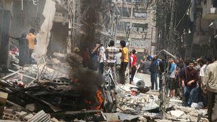 La population d'Alep (Syrie) inspectent les bâtimentsvisés par les frappes aériennes, le28 avril 2016 (ABDALRHMAN ISMAIL / REUTERS)
