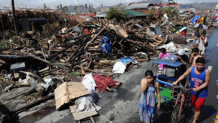 Des habitants de Tacloban (Philippines) marchent au milieu des ruines, le 10 novembre 2013. (TED ALJIBE / AFP)