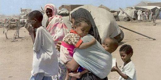 Erythréenne portant ses deux enfants dans un camp de réfugiés près de Kassala (est du Soudan) (4-6-2000) (AFP - SALAH OMAR)