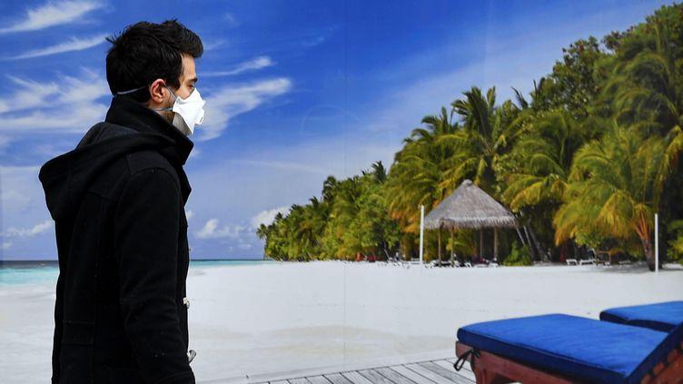 Nancy, 17 mars 2020. Une personne avec un masque de protection passe devant l'affiche d'une agence de voyage avec des palmiers, du sable blanc et la mer, lors du premier jour de confinement national pour lutter contre la pandémie de Covid-19. (MAXPPP)