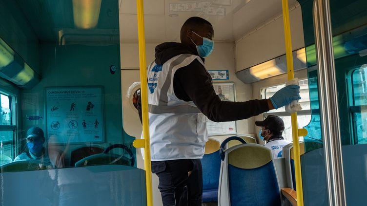 Un homme désinfecte des surfaces du RER D, pour éviter la propagation du covid 19, à Paris, le 22 mai 2020. (VALENTINA CAMU / HANS LUCAS)