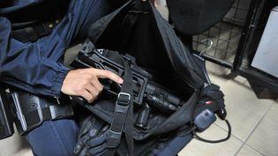 Un gendarme en civile tient entre ses mains unlanceur de balles de défense, le 13 décembre 2013, en Guadeloupe. (ARNAUD BEINAT / MAXPPP)