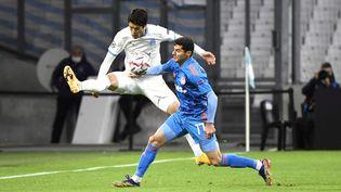 Le défenseur japonais de Marseille Hiroki Sakaietl'attaquant grec de l'Olympiakos Marios Vrousai lors du matchde Ligue des champions au stade Vélodrome de Marseille, le 1er décembre 2020. (NICOLAS TUCAT / AFP)