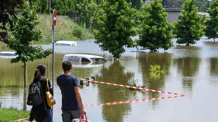 Des passants regardent les dégâts causés par les intempéries, à Louhans (Saône-et-Loire) le 17 juillet 2021. (PHILIPPE DESMAZES / AFP)