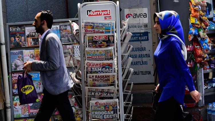 Des passants devant un kiosque à journaux à Istanbul (Turquie) (Photo d'illustration). (YASIN AKGUL / AFP)