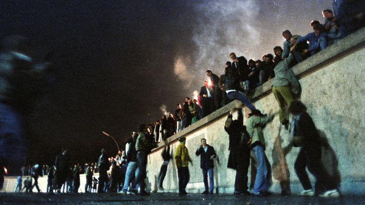 Des citoyens est-allemands grimpent sur le murde Berlin (ex-RDA), le 9 novembre 1989. (STRINGER  / REUTERS)