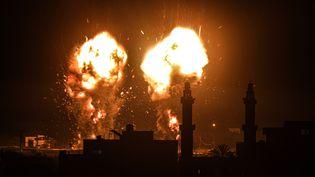 Des flammes visibles après une frappe aérienne israélienne sur des cibles du Hamas dans la bande de Gaza, le 15 juin 2021. (ALI JADALLAH / ANADOLU AGENCY / AFP)