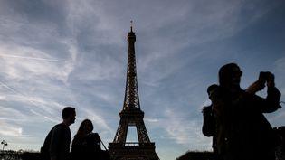 Des touriste font des selfies devant la tour Eiffel, à Paris, en octobre 2016. (PHILIPPE LOPEZ / AFP)