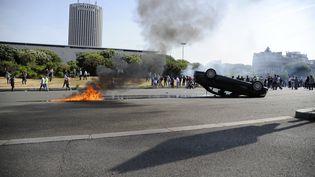 Un VTC est retourné par les taxis en colère, le 25 juin 2015 à la porte Maillot, à Paris. (THOMAS OLIVA / AFP)