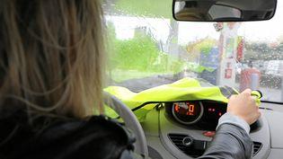 Une automobiliste dépose un gilet jaune sur son tableau de bord pour signaler son opposition à la hausse des prix du carburant, le 6 novembre 2018 à Nice (Alpes-Maritimes). (MAXPPP)