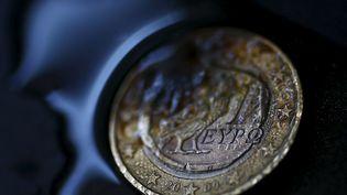 """Une pièce d'un euro grecque, portant le symbole de la chouette et l'inscription en alphabet grec """"euro"""". (KAI PFAFFENBACH / REUTERS)"""