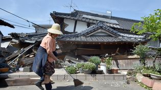 Une femme nettoie devant sa maison, dans la région de Kumamoto (Japon), qui s'est effondrée après un séisme, le 15 avril 2016. (KAZUHIRO NOGI / AFP)