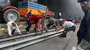 Des manifestants opposés à l'écotaxe arrachent une barrière de sécurité sur une route àPont-de-Buis (Finistère), le 26 octobre 2013. (FRED TANNEAU / AFP)