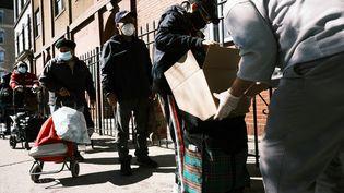 Les gens reçoivent de la nourriture à l'église chrétienne de Thessalonique lors d'une distribution le 17 octobre 2020 à New York. (SPENCER PLATT / GETTY IMAGES NORTH AMERICA / AFP)
