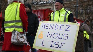 """Un """"gilet jaune"""" demande le rétablissement de l'ISF durant une manifestation à Paris, le 1er décembre 2018. (ZAKARIA ABDELKAFI / AFP)"""