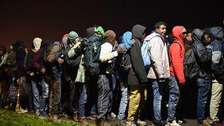 Des migrants attendent des bus pour être répartis dans différents centres en France le 24 octobre 2016 à Calais (PHILIPPE HUGUEN / AFP)