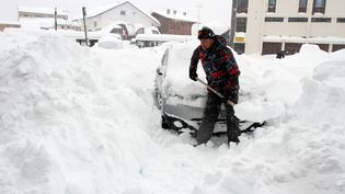 Un homme déneige sa voiture, le 1er février 2015, àSaint-Lary-Soulan, une station de ski des Hautes-Pyrénées. (LAURENT DARD / AFP)