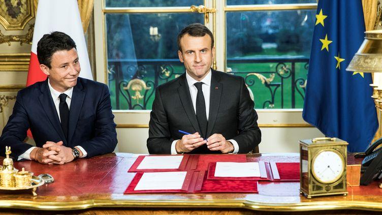 Le président de la République, Emmanuel Macron, signe trois textes de loi, le 30 décembre 2017, à l'Elysée, à Paris, aux côtés de Benjamin Griveaux, porte-parole du gouvernement. (ETIENNE LAURENT / AFP)