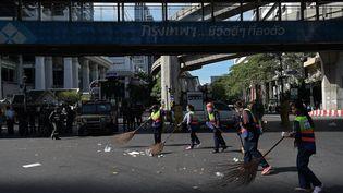 Des personnes balaient les débris après l'attentat de lundi 17 août à Bangkok (Thaïlande), mardi 18 août 2015. (CHRISTOPHE ARCHAMBAULT / AFP)