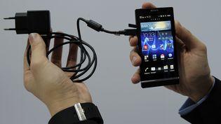 Un homme tient un chargeur sur un smartphone de la marque Sony, le 28 février 2012 à Barcelone (Espagne). (LLUIS GENE / AFP)