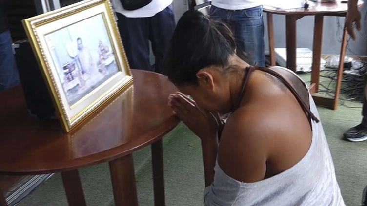 Une Thaïlandaise se prosterne devant un portrait duroiBhumibol Adulyadej, le 16 octobre 2016, trois jours après sa mort. Elle avait été arrêtée pour des messages critiques envers la monarchie. (AP / SIPA)