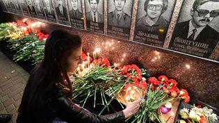 Une jeune femme allume une bougie près du monument en hommage aux victimes de la catastrophe, àSlavutych (Ukraine), le 26 avril 2019. (GENYA SAVILOV / AFP)
