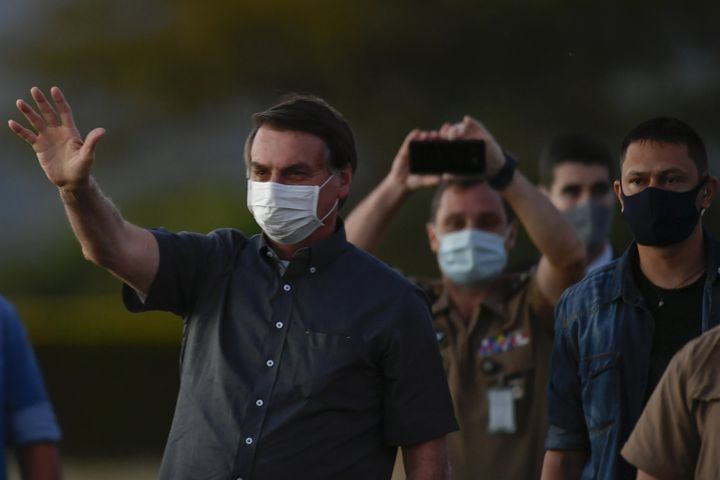 Brazilian President Jair Bolsonaro greets visitors on July 20, 2020, from the garden of the Presidential Residence, where he is isolated.  (MATEUS BONOMI / AGIF)