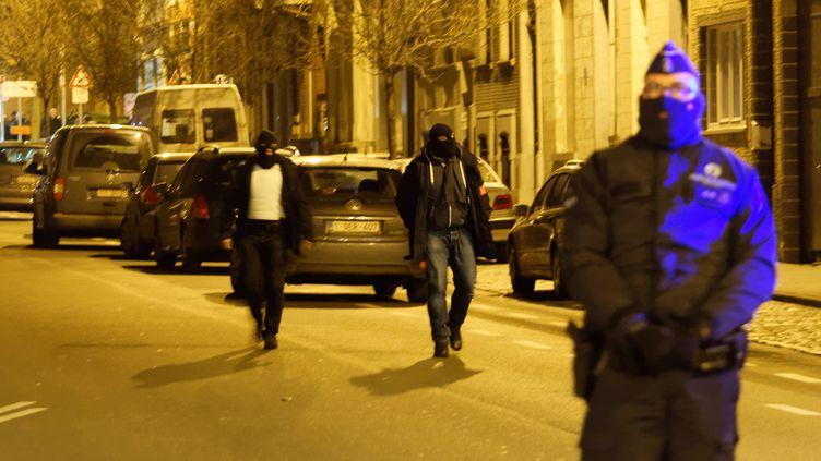 Des policiers perquisitionnent dans un quartier de Bruxelles, le 30 décembre 2015. (CITIZENSIDE / OLIVIER GOUALLEC / AFP)