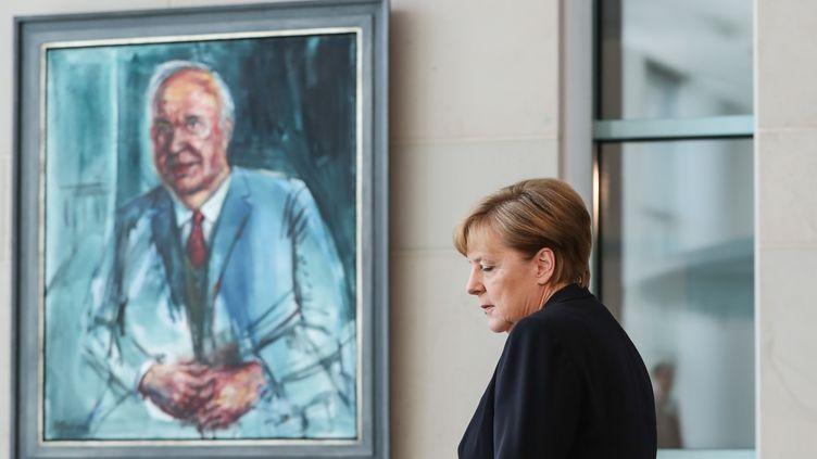 La chancelière allemande Angela Merkel devant un portrait d'Helmut Kohl, le 18 juin, à Berlin. (SHAN YUQI / XINHUA / MAXPPP)