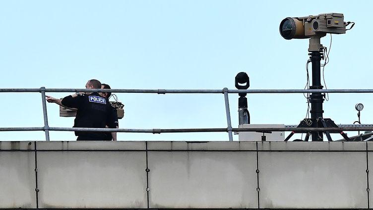 Des policiers britanniques à l'aéroport de Gatwick, au sud de Londres, le 21 décembre 2018, après l'intrusion de drones. (BEN STANSALL / AFP)