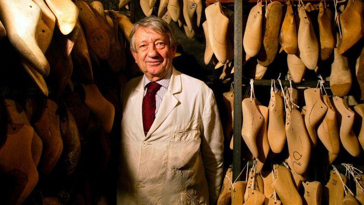 Le bottier Raymond Massaro pose près des formes utilisées pour la fabrication de chaussures dans la cave de son atelier, octobre 2003 à Paris  (JEAN-PIERRE MULLER / AFP)