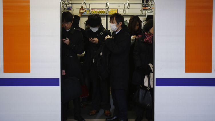 Des Japonais montent dans le train à Tokyo (Japon), le 14 février 2013. (YUYA SHINO / REUTERS)