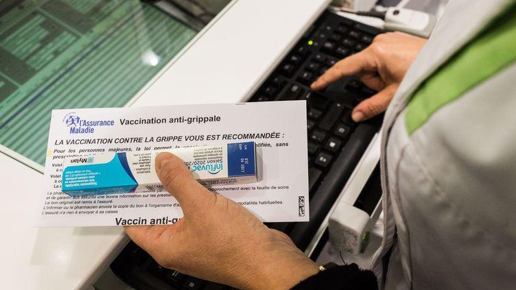 Une pharmacienne délivre un vaccin contre la grippe dans une pharmacie de Ribérac (Dordogne), le 14 octobre 2020. (BURGER / PHANIE / AFP)