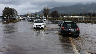Des voitures tentent de circuler sur une route près de l'aéroport d'Ajaccio, malgré les inondations qui frappent la ville, le 21 décembre 2019. (PASCAL POCHARD-CASABIANCA / AFP)