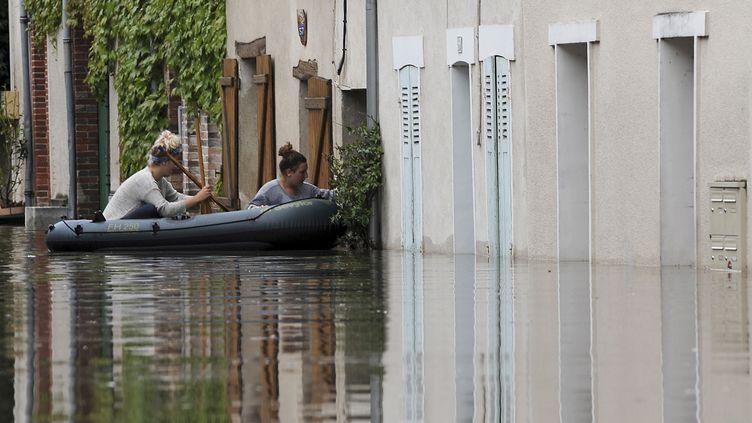 Deux femmes tentent d'entrer dans leur domicile inondé, à Montargis (Loiret), le 1er juin 2016. (GUILLAUME SOUVANT / AFP)